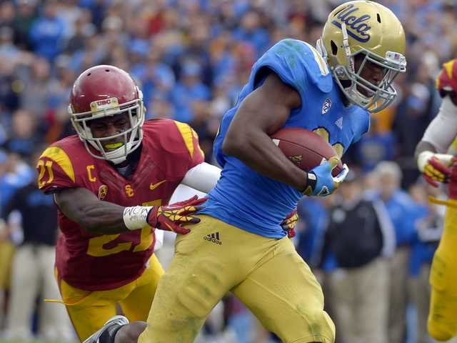 UCLA running back Johnathan Franklin, right, runs in for a touchdown during the game, Saturday, in Pasadena.