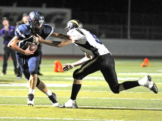 Trinity Classical Academy running back Spencer Klehn (4) fends off a tackle by Joshua Springs' Dylan Hadley in a CIF-Southern Section 8-Man Div. II semifinal game on Friday night at Valencia High.