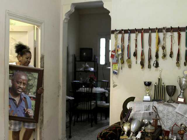 Maria Victoria Gil negotiates through a doorway a large framed portrait of her son, swordsman Elvis Gregory, in Havana, Cuba, Friday.