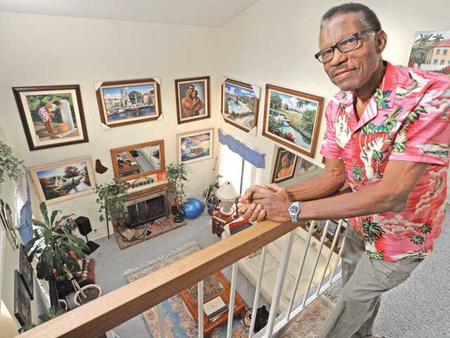 Romeo Downer looks down on his living room and his art-covered walls in his Canyon Country home.