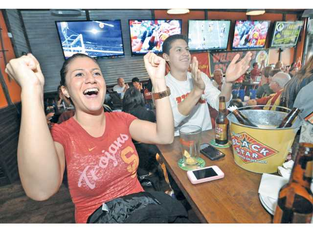 USC fans Josephine Broers, left, and Michael Bohorquez cheer as USC scores a touchdown in the first half as they attend the USC Alumni Club of Santa Clarita event held at Big Wangs sports bar in Valencia on Saturday.
