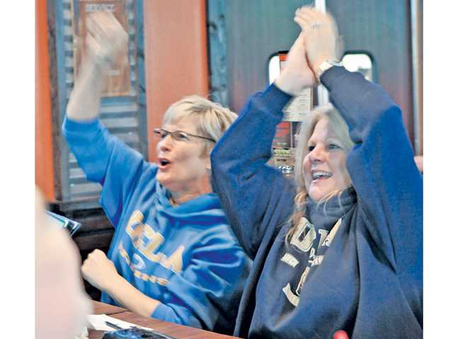 UCLA fans Kathryn Spula, left,  and Cindy Borland cheer as their team scores a touchdown in the first half against USC as they watch the game on TV at Big Wangs sports bar in Valencia on Saturday.