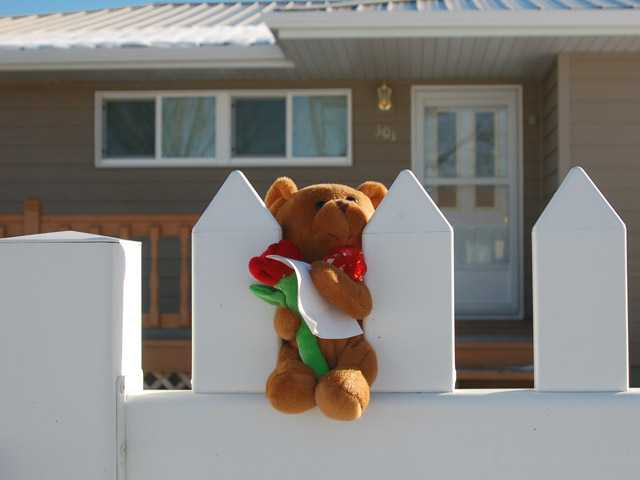 A stuffed bear is placed on a white picket fence on Monday in New Town, N.D.