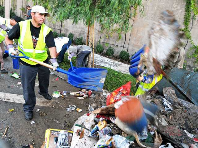 Jorge Rodriguez of Athens Services shovels debris into a bin. (Jonathan Pobre/The Signal)