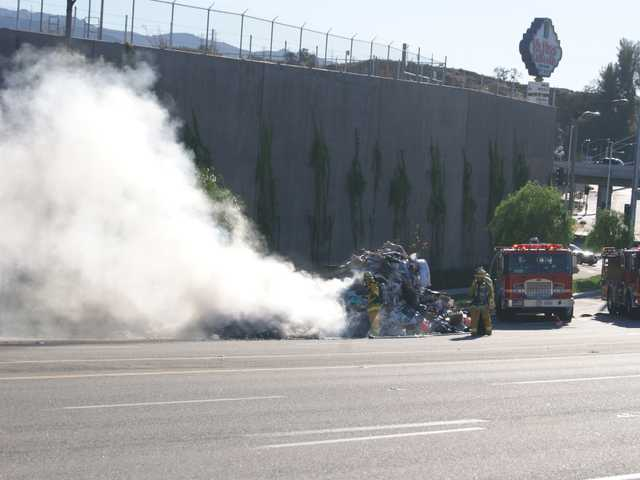 Firefighters pull away smouldering bits of trash from a burning heap dumped by a trash truck onto the south shoulder of Magic Mountain Parkway between the exit ramp of Interstate 5 and Tourney Road Monday afternoon. (Jim Holt/The Signal)