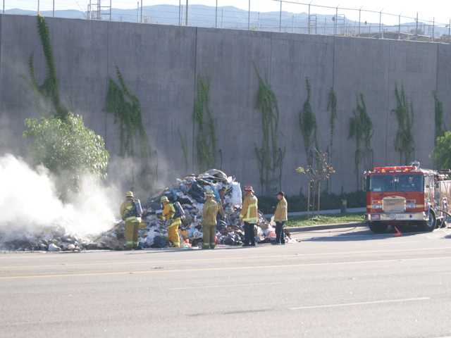 Firefighters pull away smouldering bits of trash from a burning heap. (Jim Holt/The Signal)