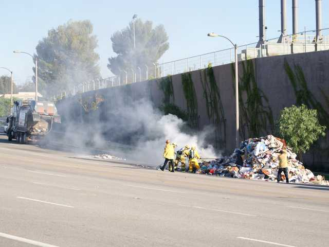 Firefighters pull away smouldering bits of trash from a burning heap dumped by a trash truck on Monday. (Jim Holt/The Signal)
