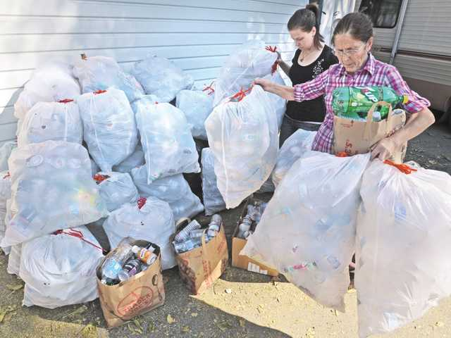 Mariana Flick, 27, left, and her mother Siv Flick move bags of bottles and cans from their driveway to be taken to the recycling center on Nov. 7.