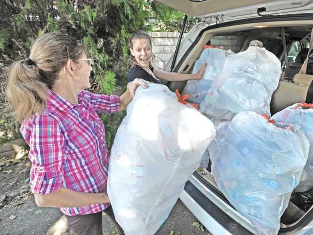Mariana Flick, 27, right, and her mother Siv Flick load bags of bottles and cans into their car to be taken to the recycling center on Nov. 7.