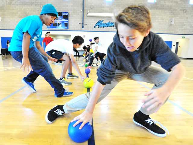 Eighth-graders Bren Lee, left, and Ryan Holland, both 13, dash to grab dodgeballs as they play in a tournament at Rancho Pico Junior High School in Stevenson Ranch on Monday.
