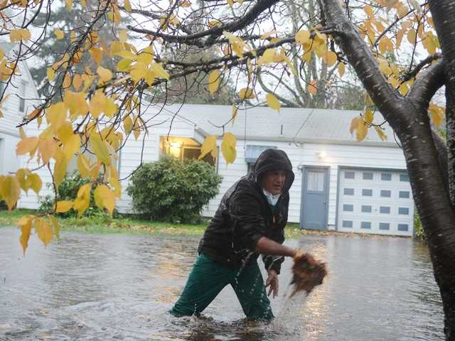 Ray Lunt wades in high water to clean out the storm drains on Nob Hill Street SE in Salem, Ore., on Monday.