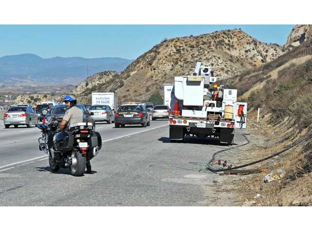 A California Highway Patrol officer watches as the northbound lanes of Highway 14 are reopened south of Newhall Avenue on Tuesday morning. (Jonathan Pobre/The Signal)