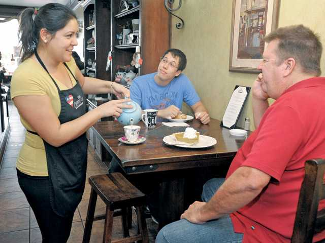Hillo, left, serves customers Chris, center,  and Joseph Hosea of Newhall at the Coffee House. The shop is often  serving local groups and clubs