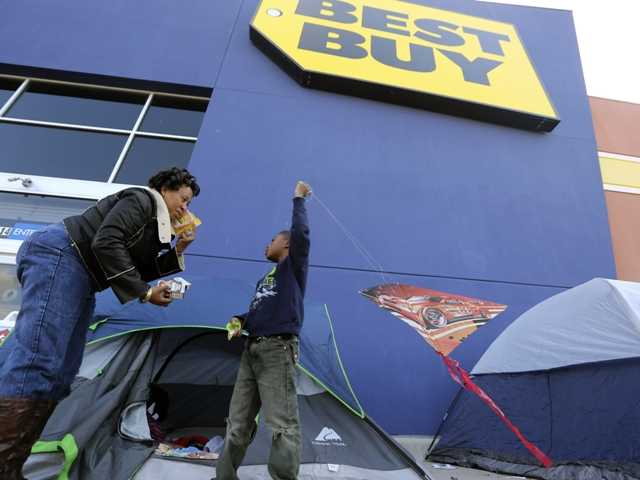 Denise Smith-Lad, left, asks her grandson Jordan Smith, 6, what he would like to eat as they camp in front of a Best Buy store in Cockrell Hill, Texas. Best Buy Co. reported another dismal quarter on Tuesday, Nov. 20.