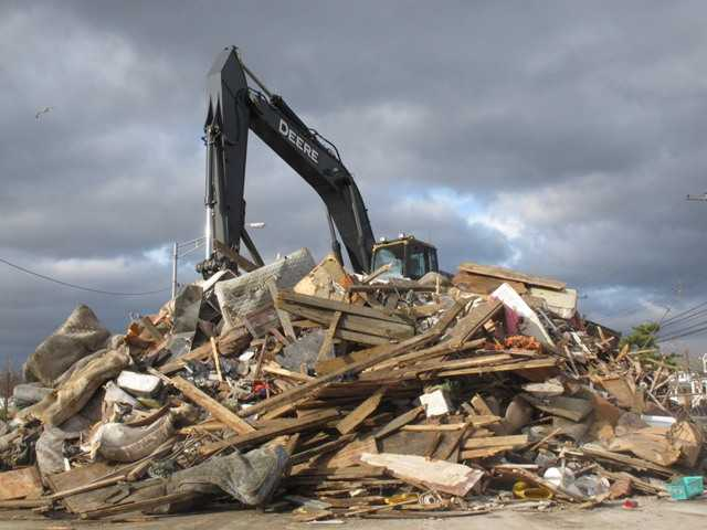 A crane sits atop a pile of storm debris in a parking lot in Point Pleasant Beach N.J. Superstorm Sandy created tons of debris that towns in New York and New Jersey are still struggling to dispose of weeks later.