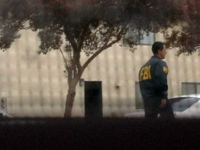 This provided photo taken Friday, Nov. 16, 2012, by Jenny Collins from her neighbor's window shows an FBI agent during a raid at the home of 21-year-old Miguel Alejandro Santana Vidriales of Upland, Calif.