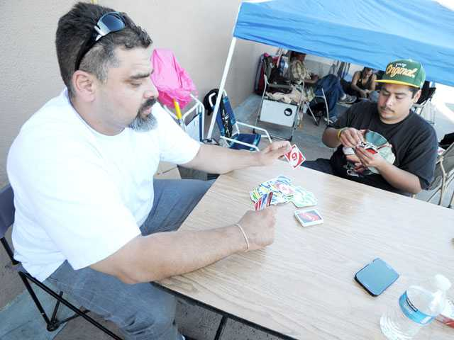 Robert Estrada, left, and Victor Granados play a game of Uno to pass the time outside the Best Buy store in Saugus on Tuesday.  (Jonathan Pobre/The Signal)