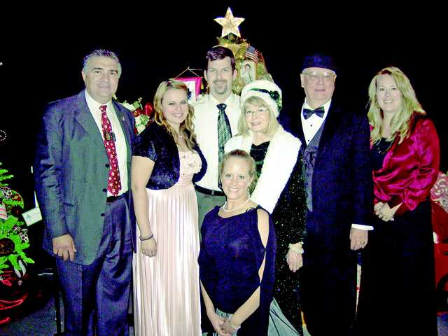 Left to right, Dante Acosta, Heather Sandnes, Eric Larson, Myrna and Gary Condie and Heather Lake, Kim Larson kneels at front. The Gold Star Families tree earned $7,250 at the auction.