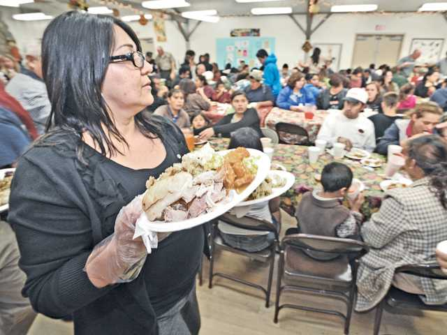 Volunteer Elizabeth Mack serves some of the 300 thanksgiving dinners to Val Verde residents at Val Verde Community Regional Park on Tuesday evening.