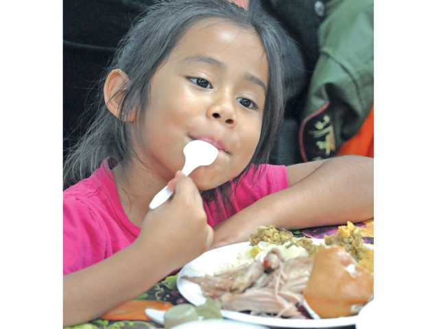 Jesse Szunigas, 5, enjoys one of the 300 Thanksgiving dinners at Val Verde County Park on Tuesday evening.