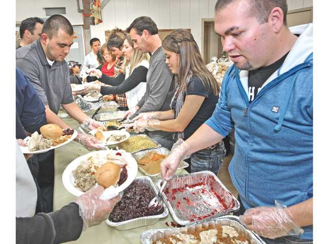 Adam Bye, right, helps serve Thanksgiving dinners for Val Verde residents at Val Verde Community Regional Park on Tuesday evening.