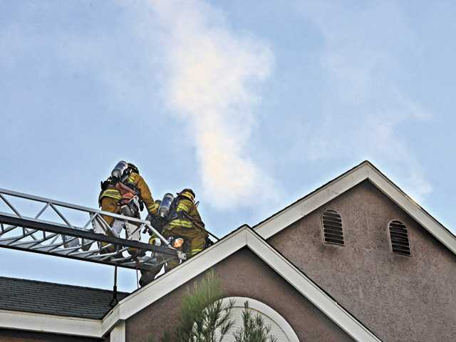 Firefighters approach the roof of a burning apartment attic as smoke escapes in Canyon Country on Wednesday. (Rick McClure/The Signal)