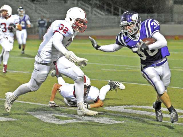 Valencia running back Stone Jackson (36) straigh-arms Paso Robles defender Josh Hayley on Nov. 9 at Valencia High School.