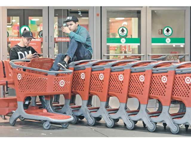 Brandon Fretwell, left, and Cole Simmons, of Saugus, are first in line as they sit on shopping carts while waiting with a small group of shoppers to buy a 32 inch LCD TV at Target on Thanksgiving night in Valencia.