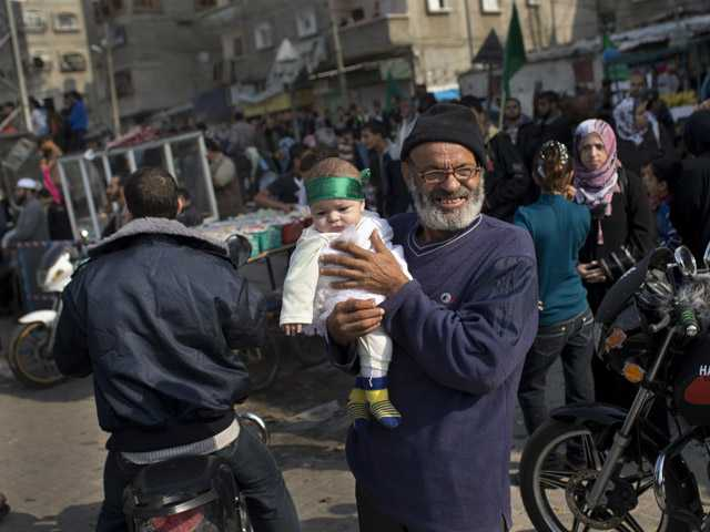 A Palestinian baby wears a Hamas bandana during a rally to celebrate the Israel-Hamas cease-fire in the Jebaliya refugee camp, north Gaza Strip, Thursday.