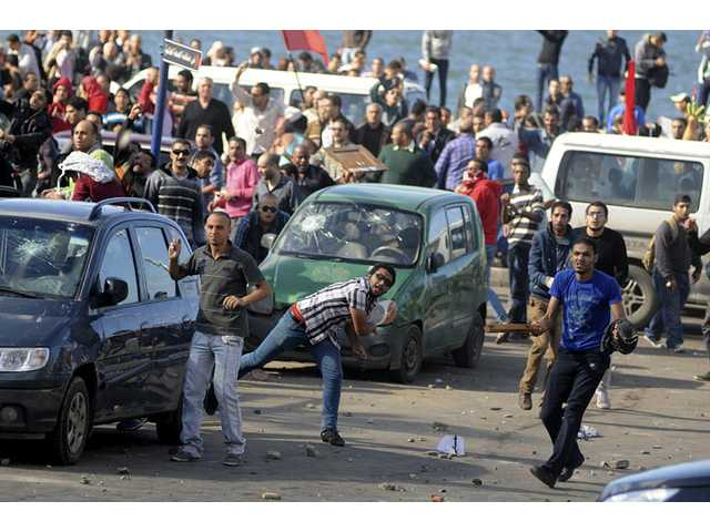 Protesters hurl stones during clashes between supporters and opponents of President Mohammed Morsi in Alexandria, Egypt.