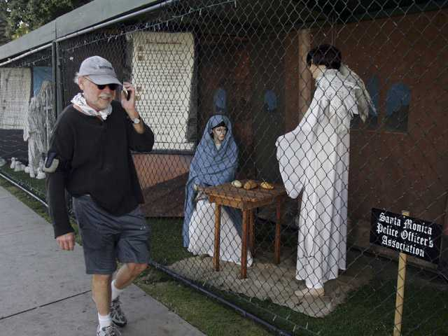 A man walks past two of the traditional Nativity scenes along Ocean Avenue at Palisades Park in Santa Monica.