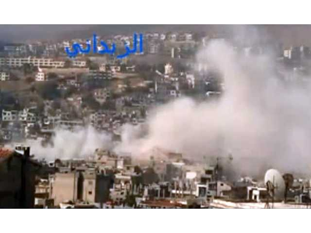 In this picture from the Shaam News Network, smoke rises from buildings due to government shelling in a Damascus suburb in Syria, on Friday.