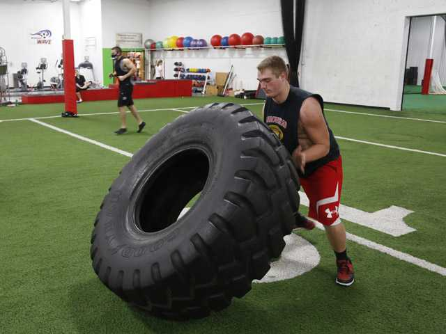 In this Oct. 26 photo, Billy Hirschfield, 16, flips a tire during a workout at NX Level, an elite training facility in Waukesha, Wis.