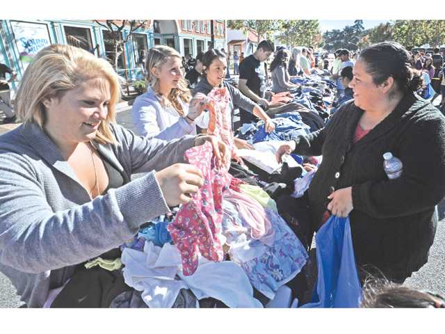 From left, volunteers Casey Horsfall and friend Meghin Schamus assist Newhall residents with children's clothes.