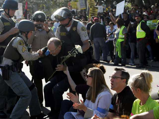 Demonstrators are arrested by police after protesting outside a Walmart store Friday Nov. 23, 2012, in Paramount, Calif. Wal-Mart employees and union supporters are taking part in today's nationwide demonstration for better pay and benefits.