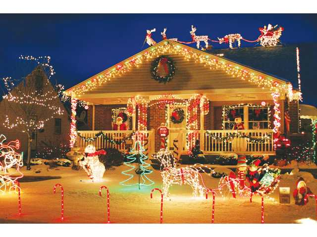 Holiday lights inside and outside the home can be an elegant, restrained sprinkling around a door or a more exuberant display of illumination, such as the one seen above.