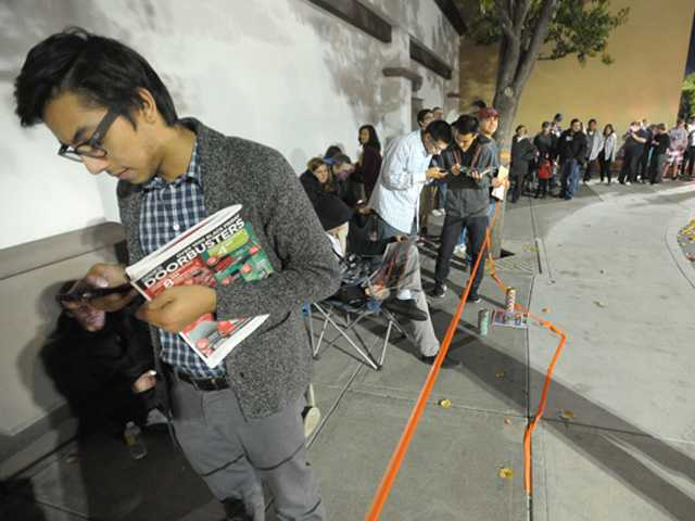 Dylan Mancillas, left, who arrived at noon stands with hundreds of shoppers as they wait for the 8 p.m. doorbuster sale at Sears in Valencia on Thursday.