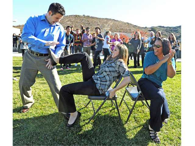 Math teacher Christy Foster, center, shoves away history teacher Doug Smith, left, as principal Erum Jones cheers during a lunchtime game of musical chairs at Rancho Pico Junior High School in Stevenson Ranch on Tuesday.