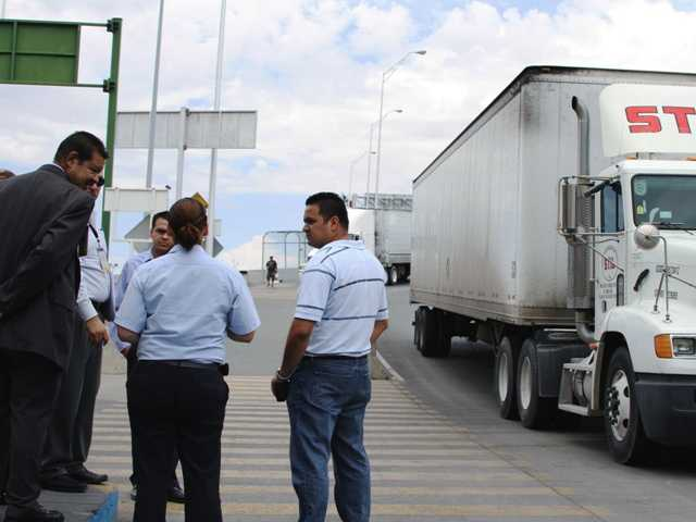 Attorney Emilio de La Rosa, left, and forensics expert Mario Gomez, right, talk to customs and court officials in Juarez, Mexico while doing a reconstruction of the events that lead to the arrest of trucker Jabin Bogan.