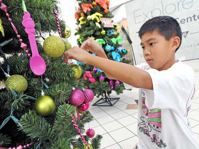 Matthew Halm, 9, decorates a Christmas tree at Westfield Valencia Town Center on Friday.