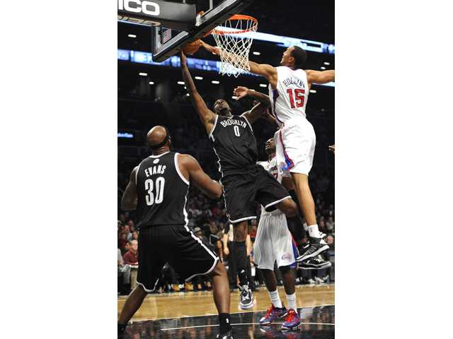 Los Angeles Clippers' Ryan Hollins (15) blocks the shot of Brooklyn Nets' Andray Blatche (0) as Nets' Reggie Evans (30) watches  on Friday at Barclays Center in New York.