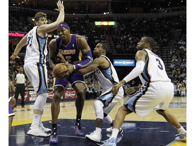 Los Angeles Lakers center Dwight Howard (12) goes to the basket against Memphis Grizzlies center Marc Gasol (33), of Spain, guard Mike Conley (11) and guard Wayne Ellington (3) in the first half of an NBA basketball game on Friday, Nov. 23, 2012, in Memphis, Tenn.