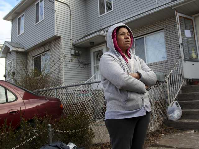 Mexican immigrant Maria Lucero stands on Nov. 14 in front of the home she rented which was damaged by Superstorm Sandy in the Midland Beach section of Staten Island, New York.