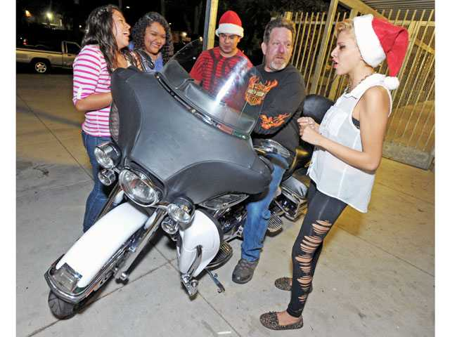 Teens from the Sierra Vista branch of the Boys & Girls Club of Santa Clarita Valley have volunteered to assist Dave Mills, sitting on bike, with the ninth annual Motorcycle Christmas Toy Run to benefit sick children at Harbor UCLA Medical Center. Left to right, Briana Loera, Genessis Galindo, Jacob Thompson, Mills and Taylor DuFour.