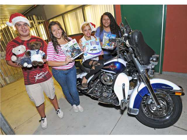Teens from the Sierra Vista branch of the Boys & Girls Club of Santa Clarita Valley have volunteered to assist Dave Mills, sitting on bike, with the ninth annual Motorcycle Christmas Toy Run.