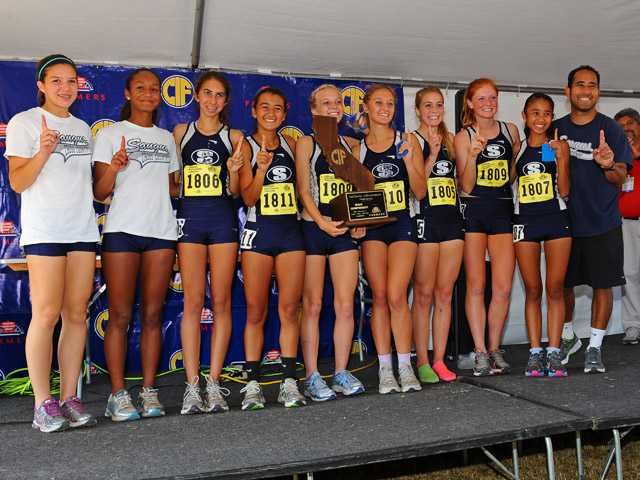 The Saugus girls team stands with its CIF State Cross Country Division II championships trophy on Saturday at Woodbridge Park in Fresno.