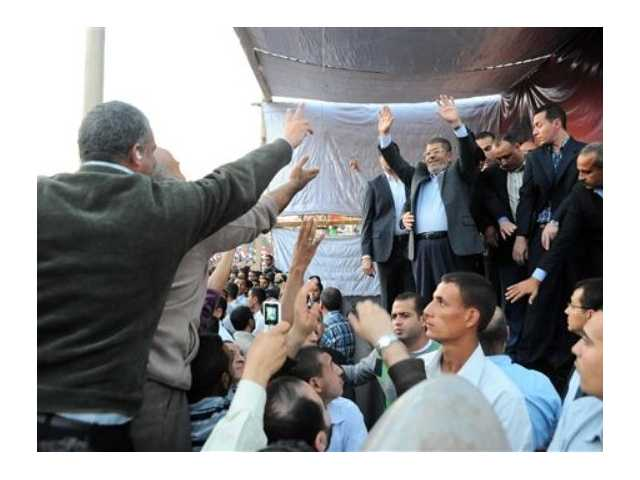 Egyptian President Mohammed Morsi, center right, waves to supporters outside the Presidential palace in Cairo, Egypt.