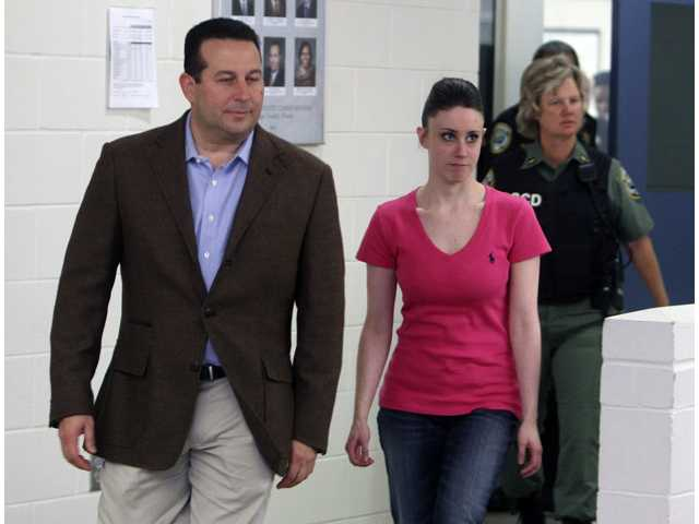 Casey Anthony, front right, walks out of the Orange County Jail with her attorney Jose Baez, left, during her release in Orlando, Fla.