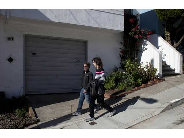 Amy Cunninghis, left, and Karen Golinski, right, walk down a street near their home in San Francisco.