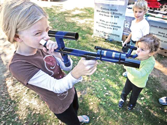 Allison Clark, 10, left, and sister Kayla, 4, right, prepare to fire Marshmallow Blasters at the SCV Street Fair at the College of the Canyons on Saturday. Brother Sean Clark, 8, looks on.